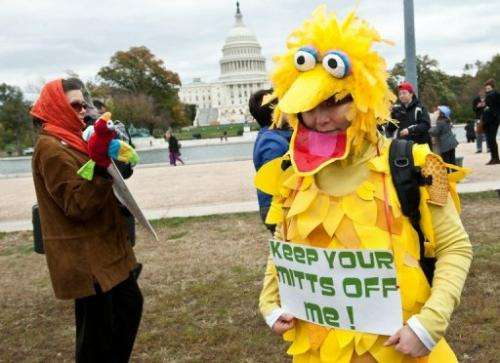 A woman wearing a costume of Big Bird holds a sign in support of public broadcasting during the