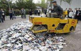 A workman drives a bulldozer over a pile of confiscated pirate audio cassettes, video cassettes, CDs and DVDs