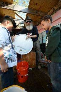 Christopher Toole leads a group of children to teach them aquaponics