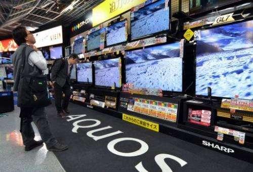 Customers check LCD television sets made at a Tokyo electronics shop on November 1, 2012