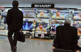 Customers watch televisions under a Sharp logo at an electrical shop in Tokyo
