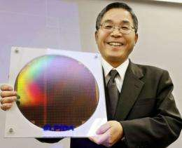 Elpida's Yukio Sakamoto shows off a 300mm silicon wafer for DRAM chips during a press conference in Tokyo in 2004