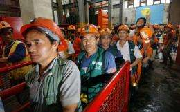 Filipino miners make their way out after their work in the mine tunnel of Philex Mining Corp. in Padcal