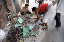 Indian youths dismantle reusable parts from electronic waste on a pavement in 2