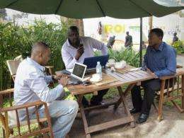 Men work on their laptops at the Endiro Cade in Kampala
