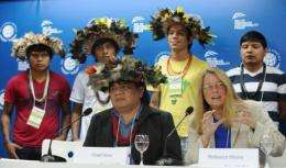 Moore (R-front) speaks alongside Brazilian Surui tribe Chief Almir (L-front) and members