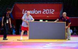 Organisers install tatamis for the judo competition at the Excel centre on July 26 in London