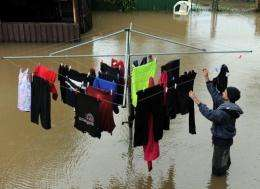 Paul Lavers salvages the laundry from his flooded backyard after heavy rains caused flash flooding across Sydney