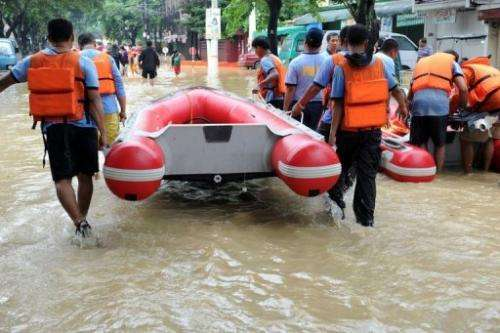 Philippine police rescue teams prepare a boat to evacuate residents