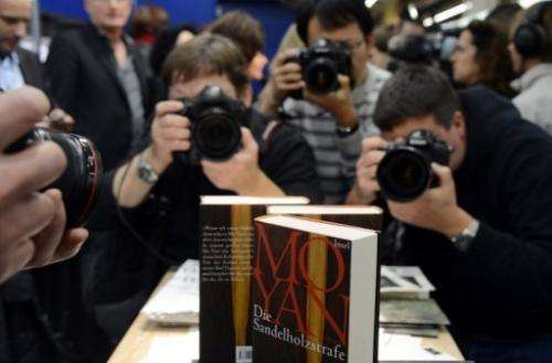 Photographers take pictures Chinese author Mo Yan's 2012 Nobel Literature Prize winning book