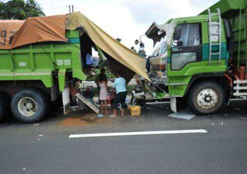 Residents affected by floods shelter near two trucks parked along a road in Quezon city
