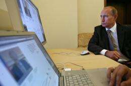 Russian President Vladimir Putin looks at a computer in his office