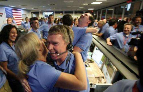 Telecom engineer Peter Ilott (C) hugs a colleague, celebrating a successful landing for NASA's Curiosity rover