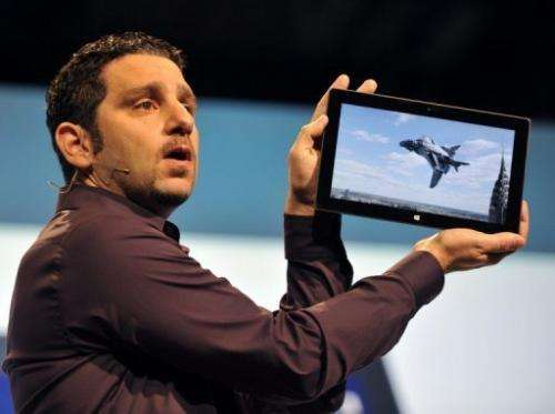 The general manager of the Microsoft Surface tablet holds up the product