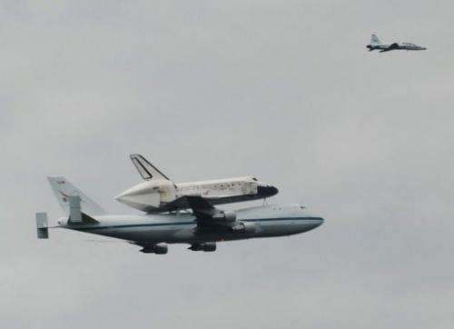 The Space Shuttle Discovery is seen above the Washington suburbs
