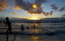 Tourists swim in Hangaroa beach as the sun sets on Easter Island, 3700 km off the Chilean coast in the Pacific Ocean