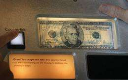 Visitors try to pick counterfeit bills from the real ones displayed at a museum in the Federal Reserve Bank of Chicago