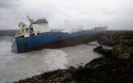 Waves break over an Italian oil tanker that ran aground