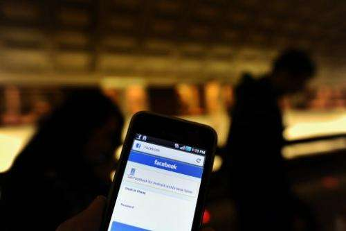 A man checks his Facebook page on his smartphone in a metro station in Washington, DC on May 9, 2012