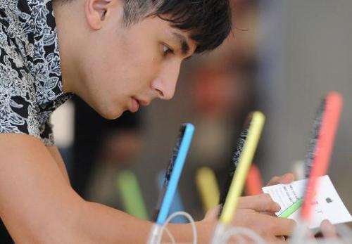 A man looks at the new iPhone 5C at the Apple Store in Glendale, California, September 20, 2013