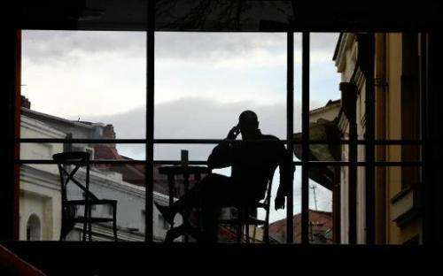 A man talks on his mobile phone as he enjoys the sunset from a roof bar in Tbilisi, March 29, 2005