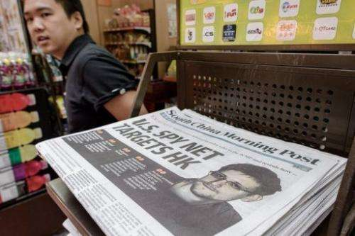A man walks past a paper carrying the story of former US spy Edward Snowden (R), Hong Kong, June 13, 2013