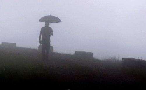 A pedestrian walks through fog in Mawsynram village in the northeast Indian state of Meghalaya, June 21, 2013