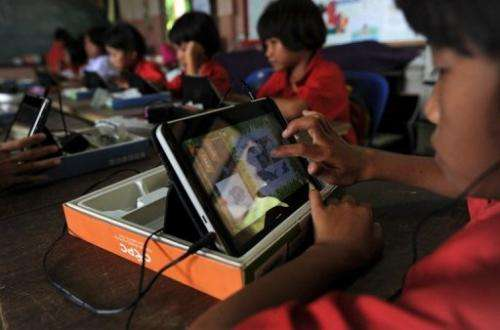 A student uses a tablet at Ban San Kong school in Mae Chan, in Thailand's northern Chiang Rai province on May 27, 2013