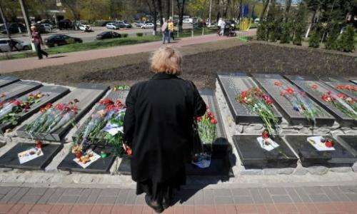 A woman looks at the signs with names of victims during a Chernobyl commemoration ceremony, Kiev on April 26, 2013.