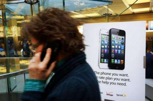 A woman walks past an Appple iPhone 5 advertisement in New York City on January 14, 2013
