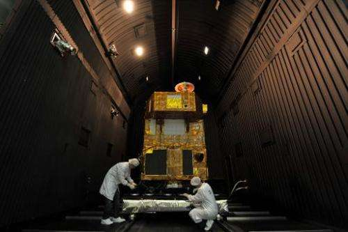 Brazilian researchers work inside a reinforced chamber on a CBERS satellite (China-Brazil Earth Resources Satellite), at Nationa