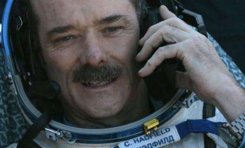 Chris Hadfield speaks on the phone shortly after landing in central Kazakhstan on May 14, 2013