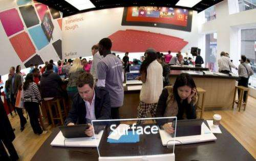 Customers get a look at products at Microsoft's pop-up store in Times Square, on October 26, 2012 in New York