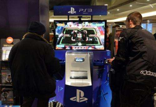 Customers try out a PlayStation 3 game console displayed at a FNAC store on November 27, 2012 in Paris