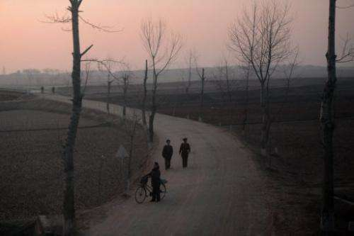 North Koreans are seen from a train on a line between Pyongyang and the North Phyongan Province,  April 8, 2012.