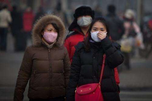 Pedestrians wearing masks wait to cross a road in severe pollution in Beijing on January 12, 2013