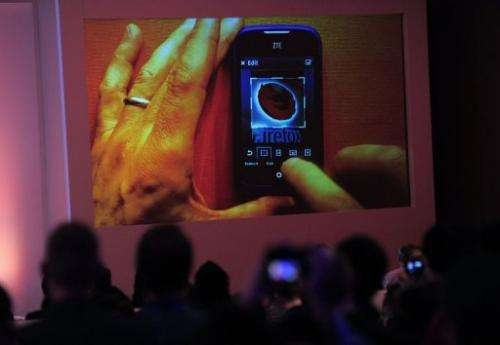 People look at a screen displaying a ZTE mobile phone with a Firefox logo in Barcelona on February 24, 2013