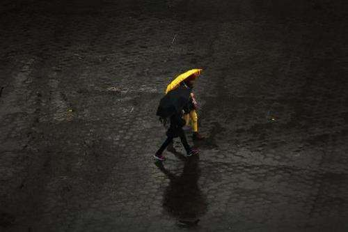 People walk in the rain through Union Square in Manhattan on November 26, 2013 in New York City
