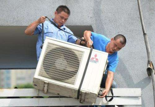 Workers install an air-conditioning unit at a food stall in Shanghai on July 2, 2013