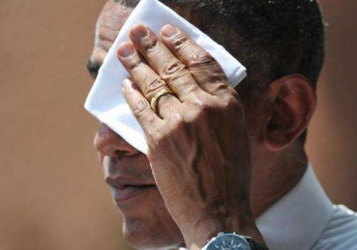 US President Barack Obama wipes his brow as he speaks on climate change in this file picture from  June 25, 2013