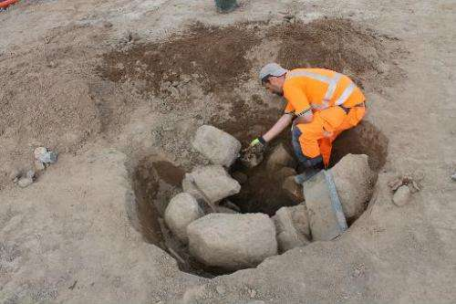 Archaeologist Anton Seiler inspects one of the foundations where there once was a wooden pole at an excavation site of the count