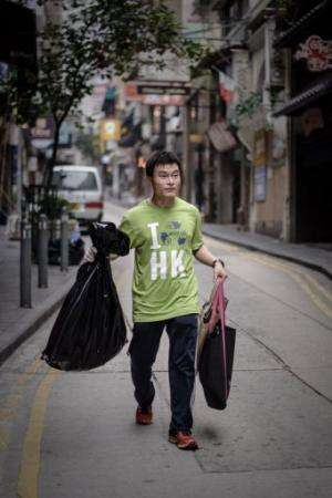 A member of the non-profit organisation Hong Kong Recycles carries bags filled with rubbish, on April 16, 2013
