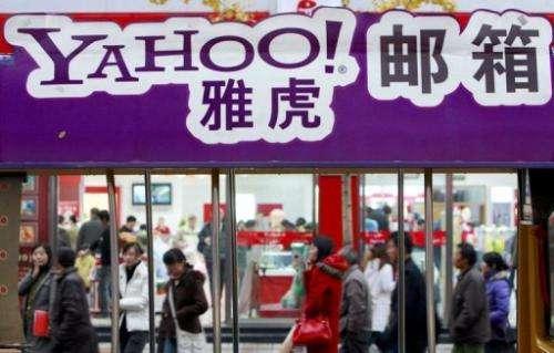 Pedestrians walk past a billboard of Yahoo in Beijing on November 14, 2007