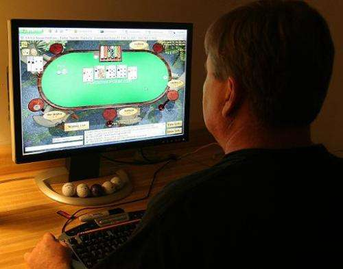 A man plays poker on his computer connected to an internet gaming site from his home in Manassas, Virginia on October 2, 2006