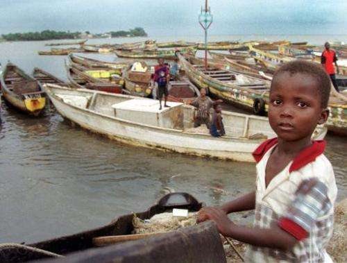 Children play on fishing boats in the harbour at Conakry, Guinea, on August 10, 1999