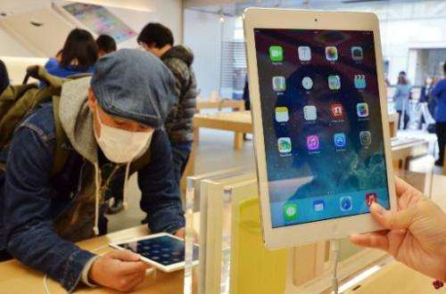 Customers try out Apple's new iPad Air tablets at an Apple store in Tokyo on November 1, 2013