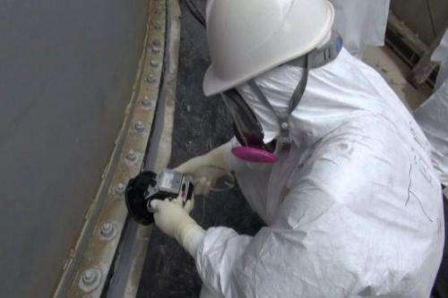 Image taken by TEPCO on September 4, 2013 shows a man checking radiation levels at a water tank at the Fukushima plant