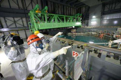 In this file photo, Fukushima Governor, Yuhei Sato (in orange helmet), inspects the spent fuel pool in the unit 4 reactor buildi
