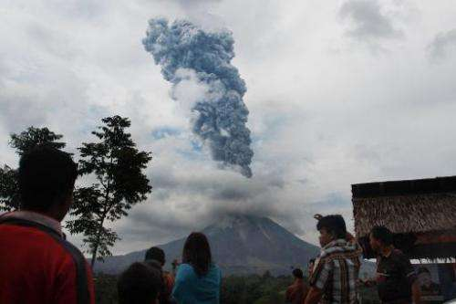 Local residents watch as a giant plume of steam and ash rise and hot lava rolls from the crater of Mount Sinabung volcano, durin