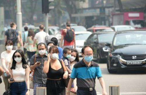 People wear face masks on Orchard Road in Singapore on June 22, 2013